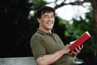 Man sitting on bench in park, reading, looking at camera smiling - Yukmin