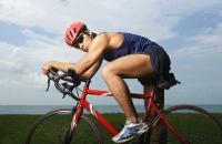Man riding bike along ocean, looking at camera - Yukmin