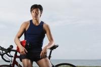Man resting on bike along ocean, looking at camera - Yukmin