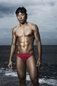Muscled man in swim trunks by ocean - Yukmin