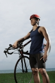 Man holding bike along ocean, wearing helmet, workout - Yukmin