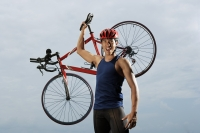 Man raising bike over shoulders, happy, finished race, looking at camera - Yukmin