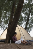 Man leaning against tree working on laptop, camping - Yukmin