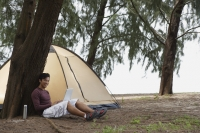 Man leaning against tree holding laptop, camping on beach - Yukmin