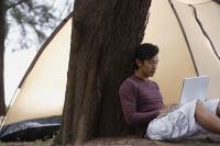 Man leaning against tree, working on laptop, camping - Yukmin