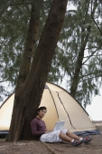 Man leaning against tree holding laptop, tent in background - Yukmin