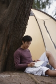 Man leaning against tree writing in journal, notebook, with tent in background, camping - Yukmin