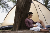 Man leaning against tree listening to music on MP3 player, camping with tent - Yukmin