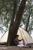 Man leaning against tree listening to music on MP3 player, tent in background, camping - Yukmin