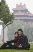 A couple smile at the camera as they sit in front of The Forbidden City, Beijing - Alex Mares-Manton