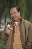 A man uses his cellphone as he stands outdoors - Alex Mares-Manton
