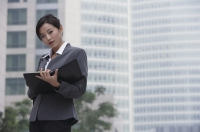 A businesswoman looks at the camera as she holds a folder - Alex Mares-Manton