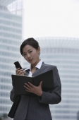 A businesswoman looks at the camera as she uses her cellphone - Alex Mares-Manton