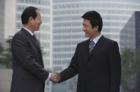 Two businessmen shake hands - Alex Mares-Manton