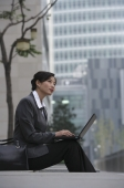 A businesswoman sits down and uses her laptop - Alex Mares-Manton