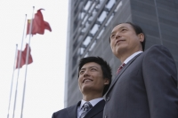 Two businessmen stand in front of a building with flags - Alex Mares-Manton