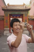 A man smiles as he takes photos - Alex Mares-Manton
