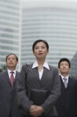 Three business professionals stand in front of a skyscraper - Alex Mares-Manton