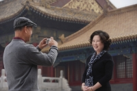 A woman smiles as she has her photo in front of The Forbidden City, Beijing - Alex Mares-Manton