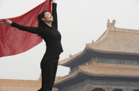 A woman holds a red shawl in the air in front of The Forbidden City, Beijing - Alex Mares-Manton