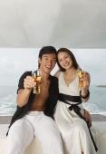 Couple on yacht, smiling at camera - Yukmin