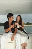 Couple on yacht, toasting with glasses - Yukmin
