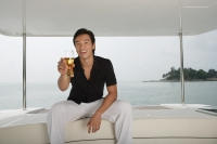 Man with glass on yacht, smiling at camera - Yukmin