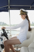 Young woman steering yacht, looking at camera - Yukmin
