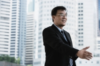 Businessman reaching out his hand for handshake - Yukmin