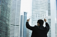 Businessman gives thumbs up, in front of skyscrapers - Yukmin