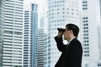 Businessman looking through binoculars - Yukmin