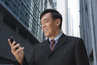 Businessman looking at mobile phone, smiling - Yukmin