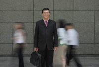 Businessman standing in crowd, looking at camera - Yukmin