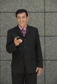 Businessman holding phone, looking at camera - Yukmin
