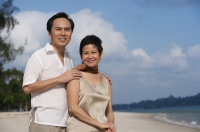 Mature couple at the beach smiling at camera - Alex Mares-Manton