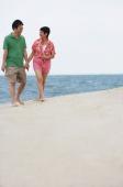 Mature couple walking at the beach - Alex Mares-Manton