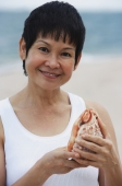 Woman with sea shell at the beach, smiling at camera - Alex Mares-Manton