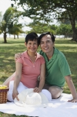 Mature couple having a picnic in the park, smiling at camera - Alex Mares-Manton