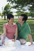 Mature couple having a picnic in the park - Alex Mares-Manton