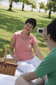 Mature couple having a picnic in the park and taking a picture - Alex Mares-Manton