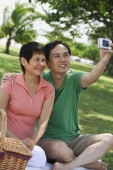 Mature couple having a picnic in the park and taking a picture of themselves - Alex Mares-Manton
