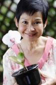 Woman with flower smiling at camera - Alex Mares-Manton