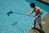 Young man cleaning swimming pool - Alex Mares-Manton