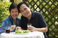 Mature couple at restaurant smiling at camera - Cedric Lim
