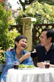 Mature couple laughing while dining in restaurant - Cedric Lim