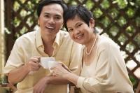 Mature couple smiling at camera while having tea - Cedric Lim