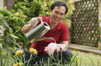 Man watering plants in the garden - Cedric Lim