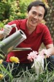 Man watering plants in the garden - Cedric Lim