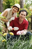 Mature couple smiling at camera while gardening - Cedric Lim