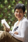 Woman relaxing with book in the garden and smiling at camera - Cedric Lim